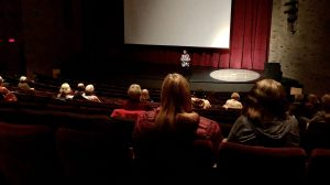 View of people in a theatre separated by distance with Valerie speaking on the stage, showing a COVID-safe Reel Monday screening